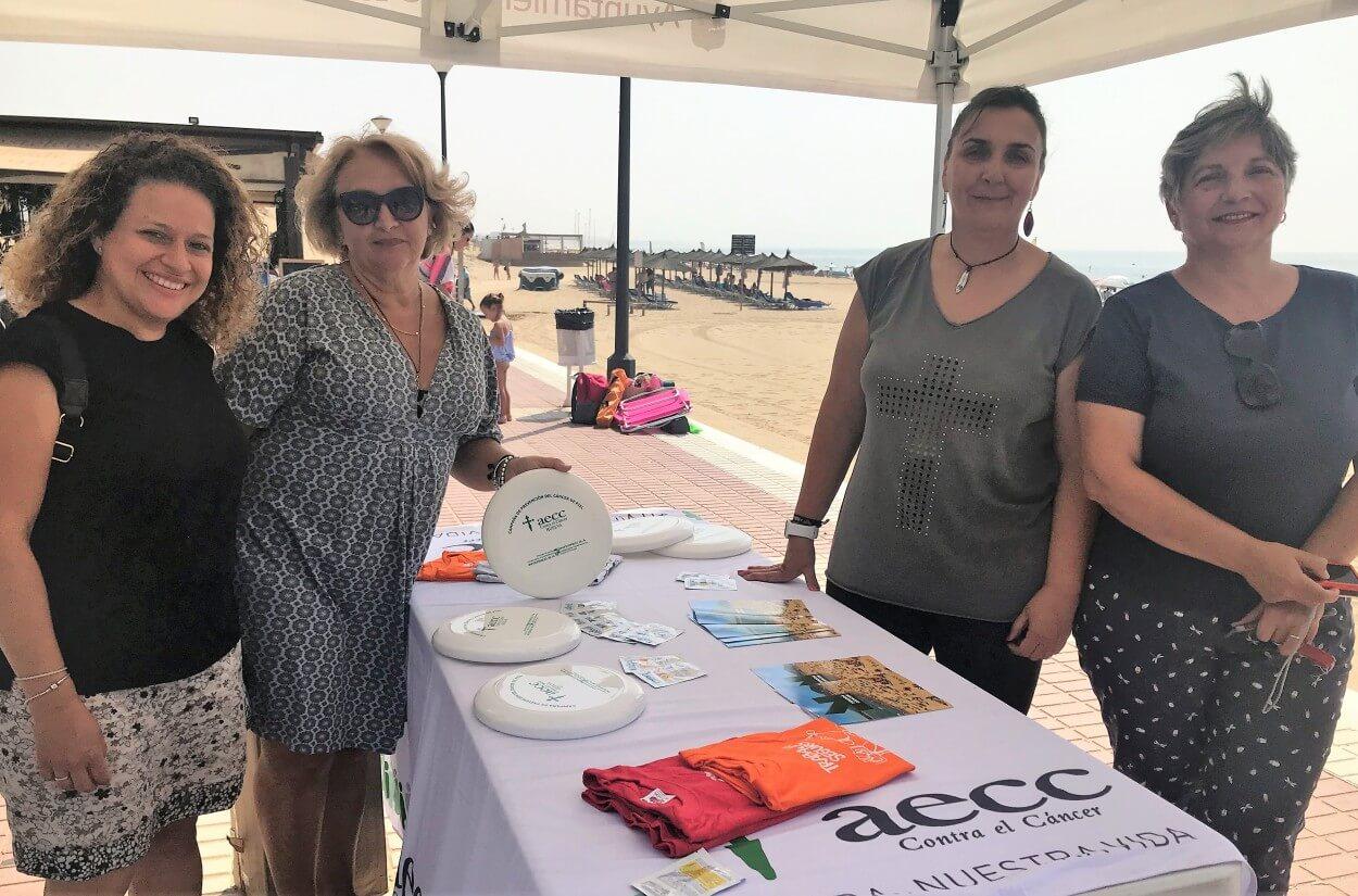 La AECC de Huelva explica a los bañistas onubenses sobre los peligros de tomar el sol